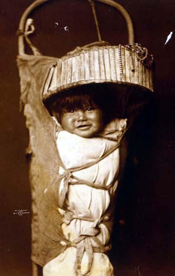 Above we show a moving photo of Apache Babe. It was made in 1903 by Edward S. Curtis.    The illustration documents An Apache infant in cradleboard.    We have compiled this collection of artwork mainly to serve as a vital educational resource. Contact curator@old-picture.com.