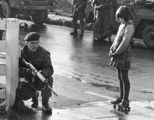Curious young girl on roller skates interrupts army patrol during the Battle of the Bogside, Northern Ireland, 1969