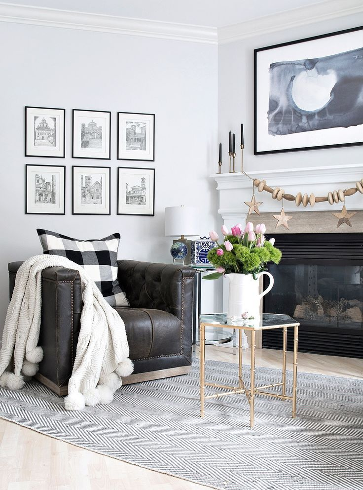 Button Tufted Leather Swivel Chairs In Front Of Fireplace With Black And White Accents And Blue Water Color Abstract Art