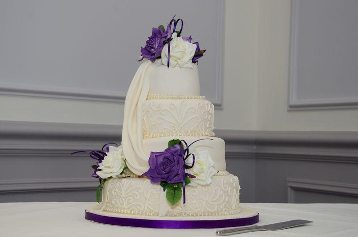 Purple roses on four tier wedding cake