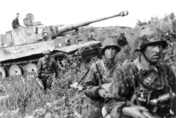 "German soldiers march before a ""Tiger"" tank during the Battle of Kursk ..."
