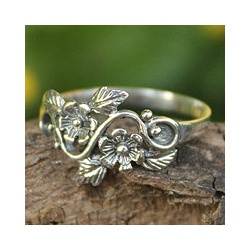 This handmade creation is offered in partnership with NOVICA, in association with National Geographic. Blushing daisies crown the feminine design of this ring from Wadarat Supasirisuk. Featuring a lea