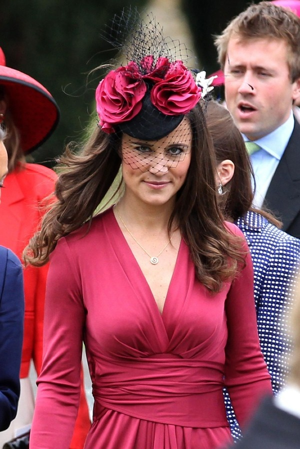 Here are 12 pics of PIPPA MIDDLETON at a Friend's Wedding in Scotland. The sister-in-law of Prince William is wearing a raspberry wrap dress with an intricate fascinator featuring three red roses and a black veil.