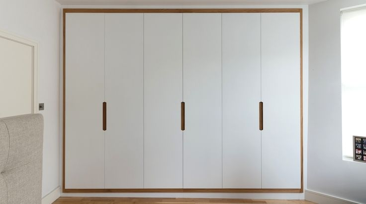 White spray lacquered full height doors with hand oiled solid oak border and handle detail.