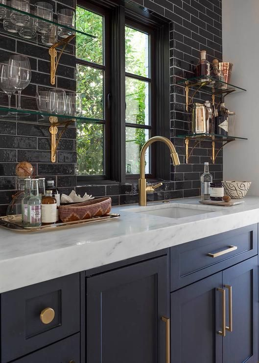 blue navy kitchen cabinets with black tile, glass open shelves with brass hardware