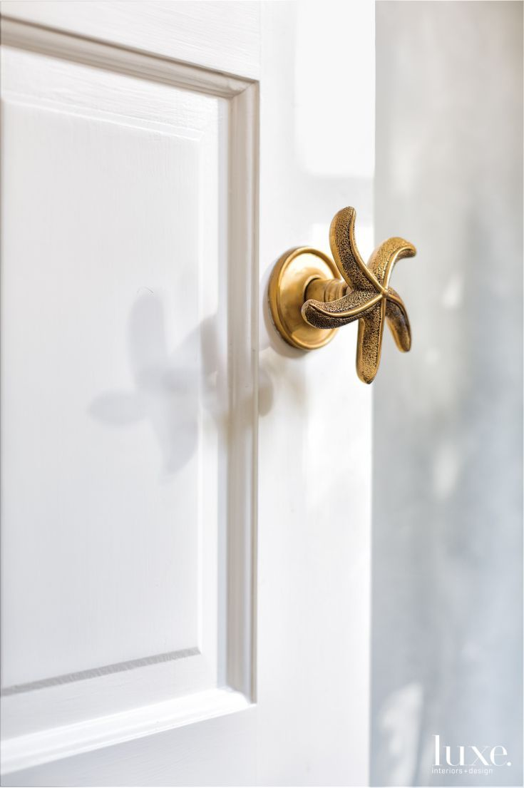 Attention to detail was paramount for both of the homes. Here, a brass starfish handle is a playful touch on a bathroom door.