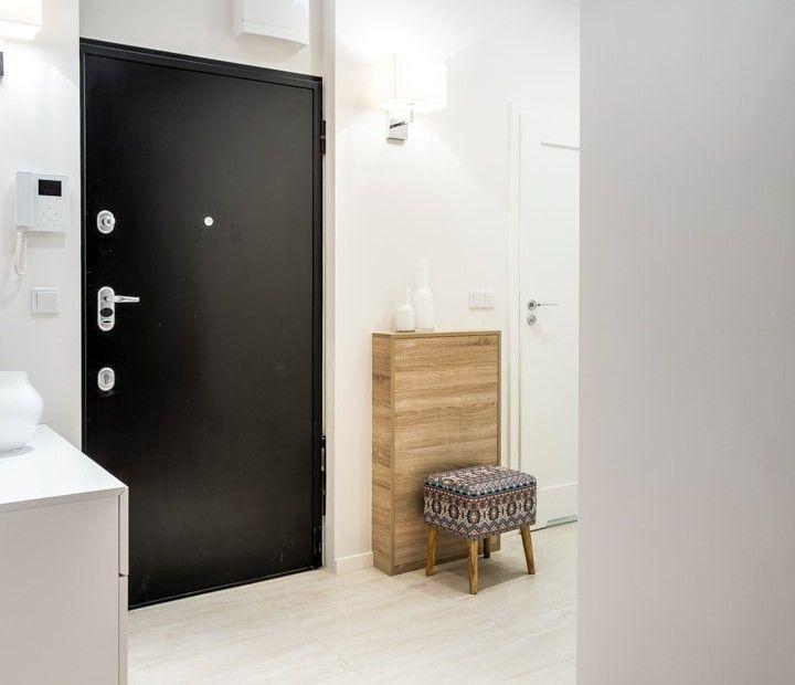 Przestronne wnętrze przedpokoju z szafką na buty i praktycznym tapicerowanym stołkiem.