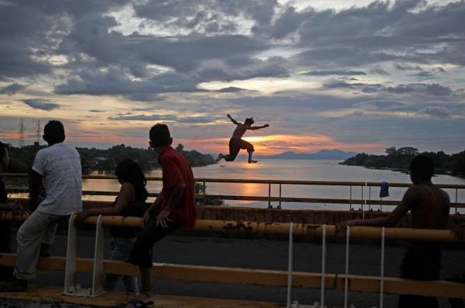 A youth jumps from a bridge into the Tipitapa River along the Pan-American Highway at sunset in Mana... - Esteban Felix/AP