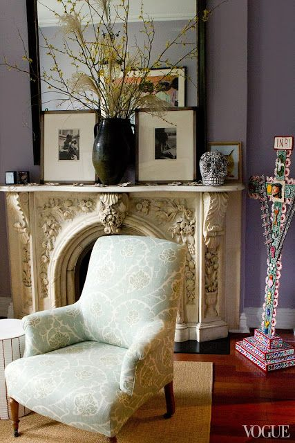 living room with lavender walls, a black mirror, framed portraits of Diego Rivera and Frieda Kahlo, and a marble fireplace mantel with a bla...