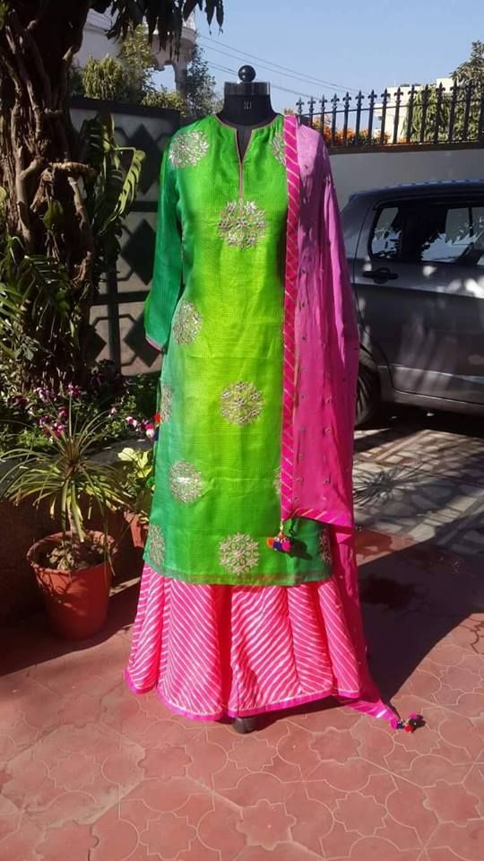 Parrot Green Chudidar with Tussar Fabric has embroidered bunches all over the dress. It is paired with pink bandhani fabric sharara.