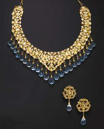 A SUITE OF INDIAN DIAMOND, TOPAZ AND ENAMEL JEWELRY  Comprising a necklace, the front designed as an openwork bib set with table-cut diamonds within foiled surrounds, the front suspending a graduated briolette-cut topaz fringe, to the polychrome enameled reverse decorated with red, green and blue floral motifs;