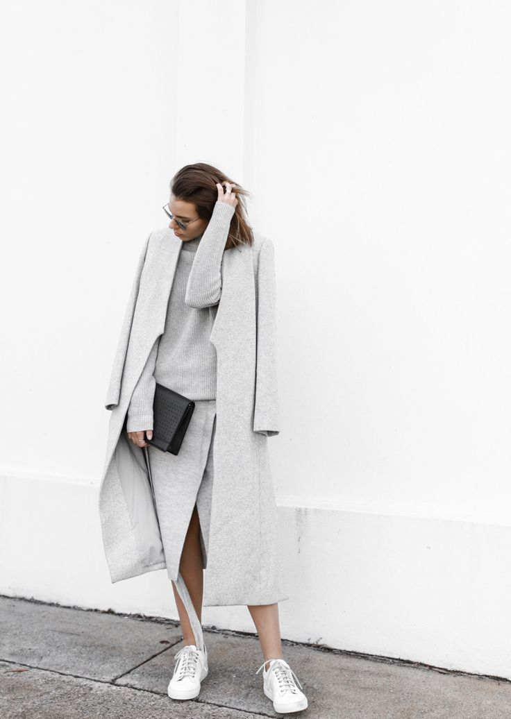 Everthing grey. White background, white sneakers and a black statement purse.