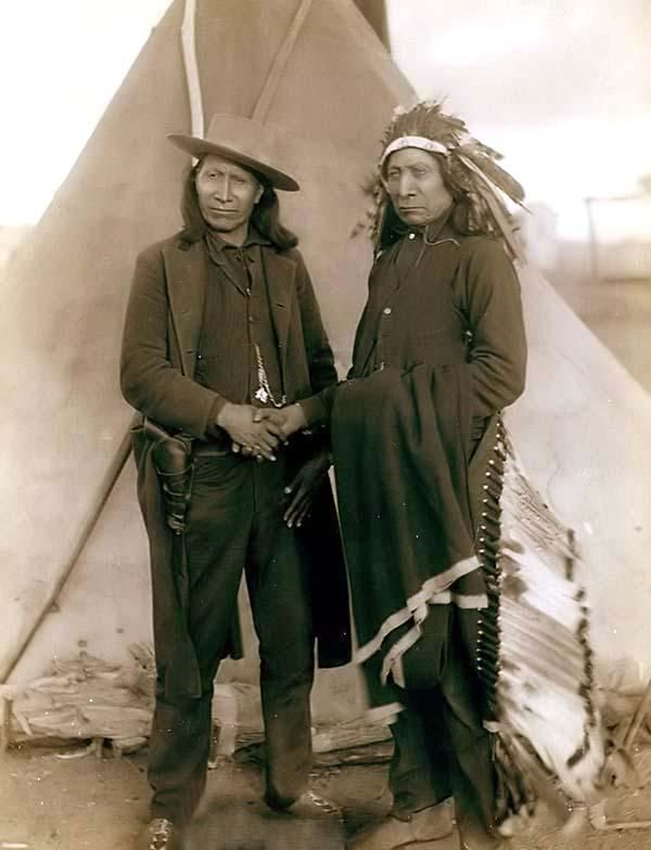 """Red Cloud and American Horse."" The two most noted chiefs of the day.  It was created in 1891 by Grabill, John C. H., photographer.The picture presents Two Oglala chiefs, American Horse (wearing western clothing and gun-in-holster) and Red Cloud (wearing headdress), full-length portrait, facing front, shaking hands in front of tipi--probably on or near Pine Ridge Reservation."