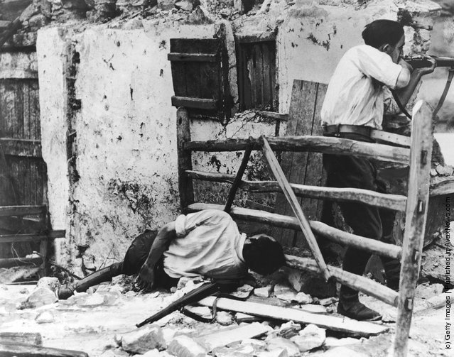 Spanish Civil War. :: A Republican farmer defending a farm on the outskirts of Irun against Nationalist forces during the Spanish Civil War, 6th September 1936. A comrade lies dead by his side. (Photo by Keystone/Hulton Archive/Getty Images)