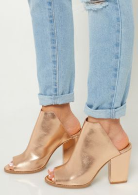 3ee8a6df6ae1 A pair of faux leather metallic mules featuring a chunky block heel ...
