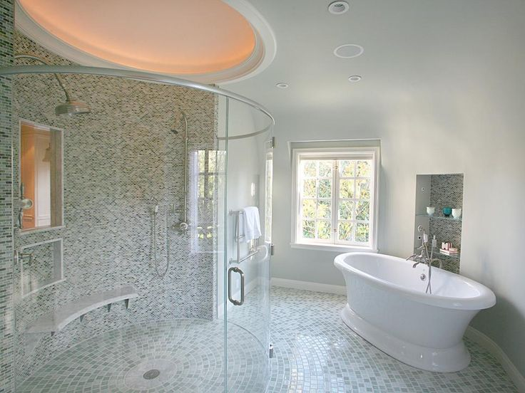 This stunning gray transitional bathroom is an homage to round and oval shapes, with its large soaking tub and gracefully curved shower and walls. Beautiful mosaic tile dresses up the shower, floor and storage cutout near the tub.