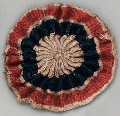 Révolution Française -    Cocarde tricolore d'officier de la Garde Nationale, tissée en laine en bandes concentriques, rouge liseré de blanc sur l'extérieur, bleu à l'intérieur et blanc au centre. Diamètre : 55 mm. BE  (La même que la précédente ?)