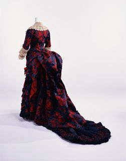 Dinner Dress, the second half of 1870s.  Brand: N. Rodrigues. Label: N. RODRIGUES Paris. Material: Blue-green silk satin brocade with woven pattern of red roses; bustle-style two-piece dress; lace at neckline, front opening and cuffs; silk satin bows at cuffs; train with silk thread fringe and wooden beads. KCI # AC9232 95-19-6AC.