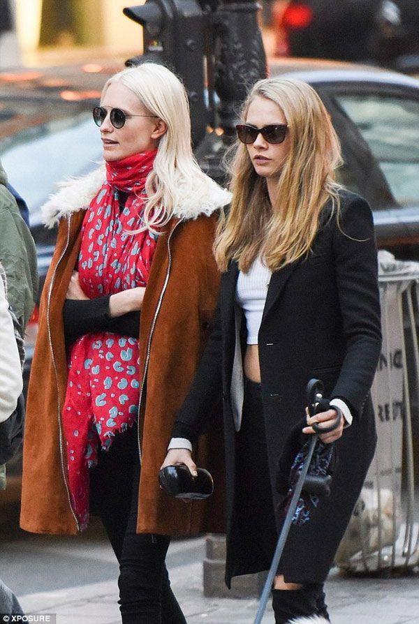 Poppy e Cara Delevingne streetstyle com skinny jeans preto, top branco, sobretudo preto e lenço vermelho.