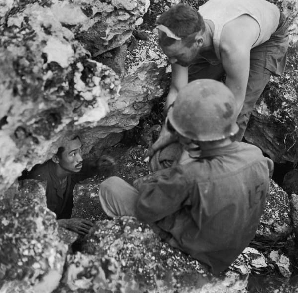 American soldiers coaxing starved, frightened civilians out of cave where they were hiding during battle for Saipan between US and Japanese forces. July 1944. Photographer:	W. Eugene Smith