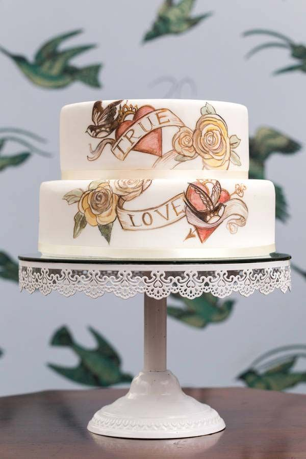 Tattoo themed artsy wedding cake..Tattoo Themed  If you and your partner are planning a vintage wedding and hate the idea of tradition, this tattoo style wedding cake from Not on the High Street is perfect! Tattooing is an art form in itself, and this is represented in the cake's romantic hand painted design. Perfect if you want a tattoo with your partner, without going through the pain of the real thing