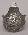"A collectable antique silver fob medallion depicting a footballer kicking a ball, and engraved ""C.R.F.U., Second Team, 1905"". The footballer has a beaded border, set on medallion shaped fob with flying scrolls. The hallmarks are clear. CRFU today stands for ""Cornwall Rugby Football Union"", but given the round ball we feel this was more likely a football rather than rugby club. Charles Winter worked between 1904 and 1911, first at Soho Metal Works and later at Soho Scientific Instrument Co."