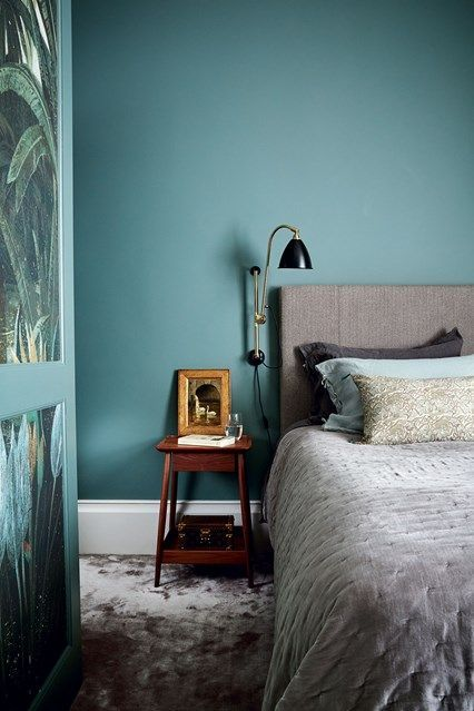 A contemporary teal Blue Bedroom with grey velvet Accessories in Bedroom Ideas. Modern blue bedroom with grey bed and carpet and wall mounted bedside light.