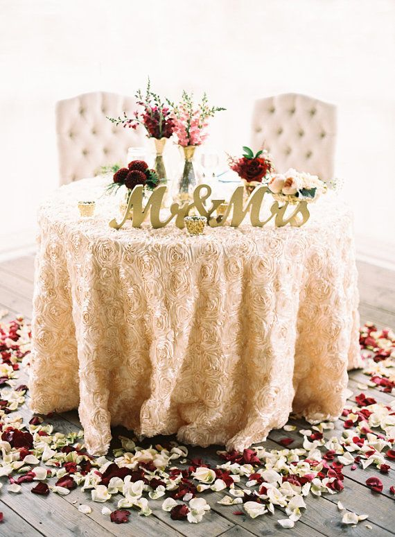 Like the sweetheart table with the textured table cloth. I also like the variation in flower colors on the floor. Not crazy about the text on the table.