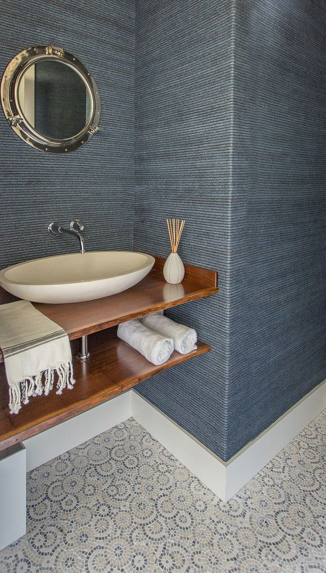 Beautiful powder room with navy wallpaper, custom vanity, wall mounted faucet and mosaic flooring.