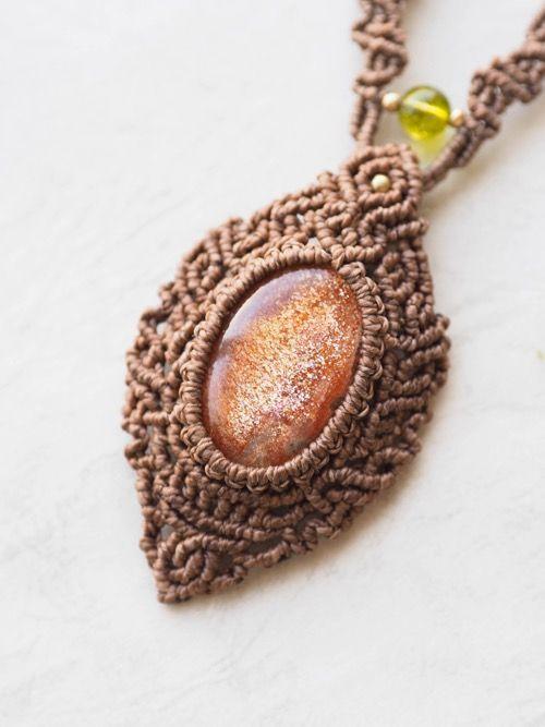 サンストーン(インド・ラジャスターン州産)・マクラメ編みネックレス紹介&販売。眩いほどの輝きが印象的なサンストーンネックレス。 石全体にびっしりとラメが詰まった、上質なサンストーンを使用しています。 首回りには鮮やかな色合いのルチルクォーツビーズと、紋章をイメージした繊細な編み目を丁寧に編みこみ、 紐エンド部分にはファイヤーアゲートビーズ&ペリドットビーズをあしらいました。 テディベア色のロウ引き糸をセレクトし、石周りから首回りまでびっしりと複雑な編み目をあしらいました。 石の持つ力強さを活かしたようなデザインで、存在感溢れる主役級のネックレスに仕上がっています。