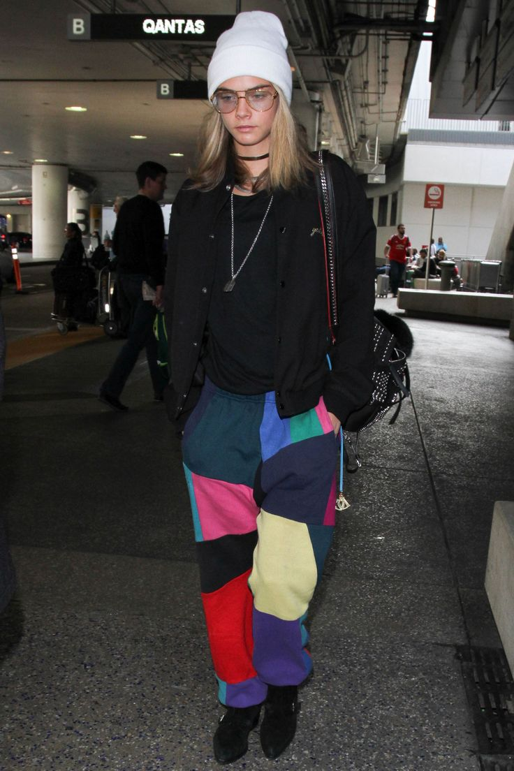 Cara Delevingne arrived at LAX airport wearing patchwork multi-coloured trousers, oversized glasses and a beanie.