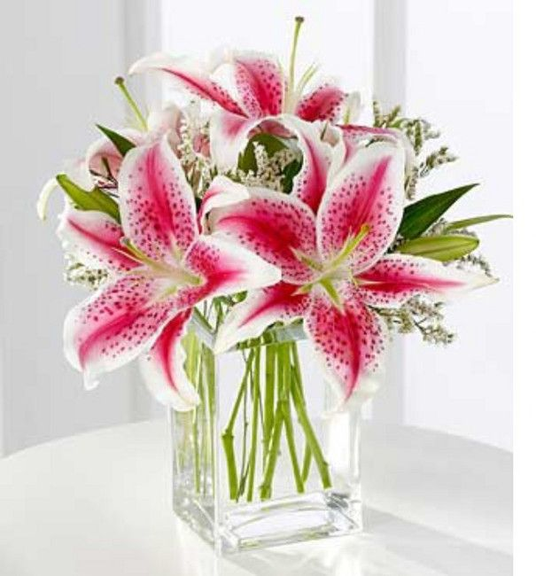 Arranjos de Flores,Jarra retangular, em cristal, onde foram colocados lírios rosa, alguns com folhas verdes, e ramos de pequenas flores silvestres brancas.