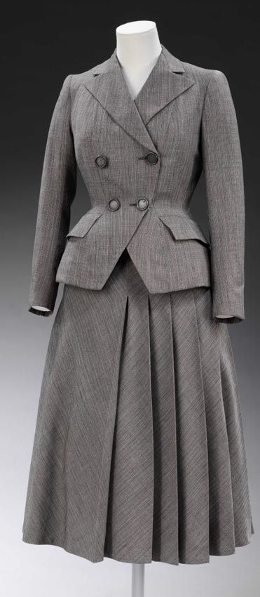 New Look Suit - Hardy Amies  Although this curvaceous suit has the small waist and wide hips typical of the New Look, the square shoulders recall wartime styles.