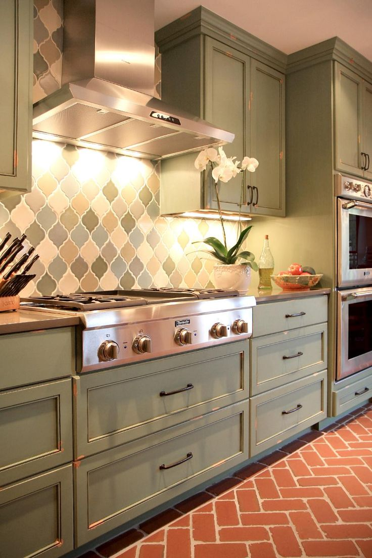 Designer Bria Hammel warms up this classic kitchen and adjacent dining room with earthy tones in the sage-green cabinets and herringbone brick floor.