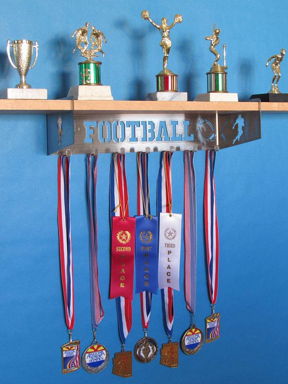 This Football Shelf makes a perfect gift especially for kids! Showcase your awards and trophies, or simply use it for a key rack and picture shelf. They come in raw metal, and are intended to be painted. Some metal may have minor imperfections since they are hand made. If you leave it as raw metal, we recommend spraying a clear coat to seal it. Wooden shelf NOT included but can be purchased at any hardware store like Home Depot or Lowes for less than $10 and is a (.75 x 5.5 x 36). Comes with…