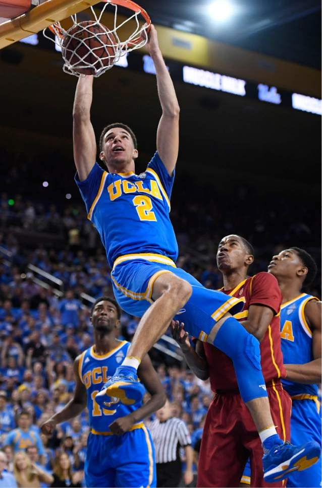 UCLA guard Lonzo Ball, center, dunks as Southern California guard Shaqquan Aaron, second from right, defends and UCLA guard Isaac Hamilton, left, watches during the second half of an NCAA college basketball game, Saturday, Feb. 18, 2017, in Los Angeles. UCLA won 102-70. (AP Photo/Mark J. Terrill)