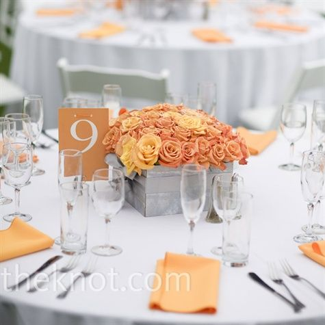 For the outdoor celebration: orange centerpieces of roses packed into square silver containers.