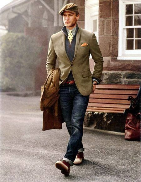Dress in a brown trenchcoat and navy blue jeans to look classy but not particularly formal. Finish off this look with oxblood leather boots.  Shop this look for $359:  http://lookastic.com/men/looks/flat-cap-longsleeve-shirt-tie-pocket-square-zip-neck-sweater-blazer-belt-trenchcoat-jeans-boots/5806  — Brown Flat Cap  — Grey Long Sleeve Shirt  — Yellow Print Tie  — Orange Pocket Square  — Navy Zip Neck Sweater  — Tan Blazer  — Brown Leather Belt  — Brown Trenchcoat  — Navy Jeans  — Burgundy…