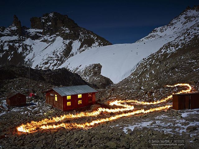 """Photograph by @simonnorfolkstudio A visualization of the receding Lewis Glacier on Mt. Kenya. A mapping of """"time's thickness"""" by pyrographically documenting glacial retreat. Using long exposures made in the middle of the night, the resultant images stem from the simple act of walking with fire along the glacier's previous boundaries... And fire, the primordial element that first provided a gathering point for human culture and, through the burning of fossil fuels, a rapidly changing climate…"""
