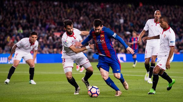Lionel Messi (C) of FC Barcelona fights for the ball with Nico Pareja (L) of Sevilla FC during the La Liga match between FC Barcelona and Sevilla FC at Camp Nou stadium on April 5, 2017 in Barcelona, Catalonia.