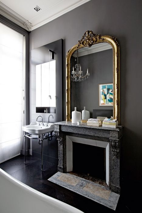 Dark Gray Walls, Gilded Antique Mirror, and Reclaimed Marble Fireplace create such a Handsome Mans Bathroom. Via Fleaing France Brocante Society.
