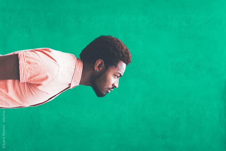 Sideway portrait of modern young hipster black man in front a green wall by Eduard Bonnin #stocksy #realstock