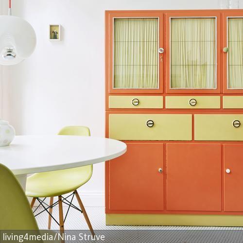 Dieser helle Essbereich, überwiegend in Weiß gehalten, wird durch limettengrüne und orangefarbene Elemente aufgepeppt. Die Eames-Chairs harmonieren dabei  …
