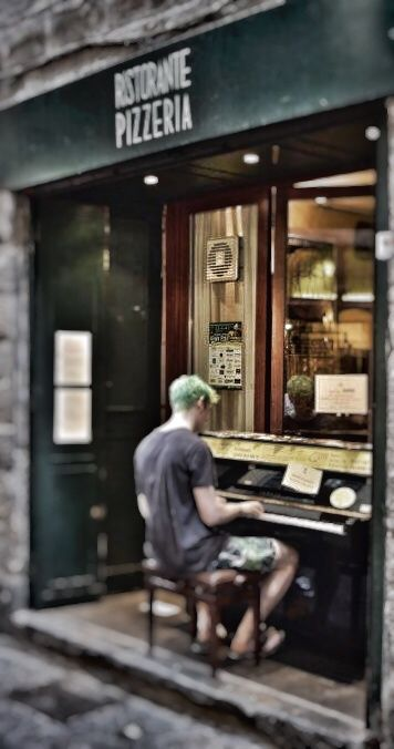 A young guy stops and starts playing the piano settled in front of a Pizzeria
