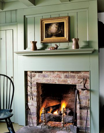 A sage green raised panel wall reveals a simple brick fireplace in this early-19th-century home.