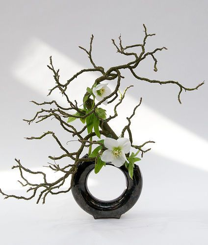 Another beautiful sogetsu ikebana arrangement.  This school typically uses either a tall, narrow vase such as one made from a bamboo stem, or a flat, open dish in which the flowers and branches are fixed in a hidden kenzan spiked support.  However, this is an example of the newer expressions of this form.