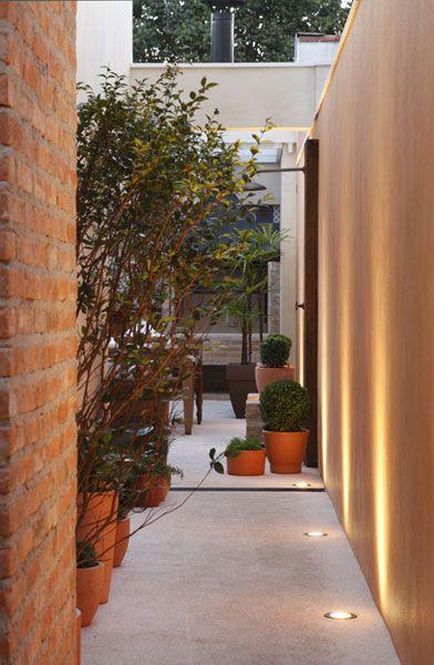 Outro ângulo do corredor lateral, que leva da entrada ao quintal com churrasqueira.