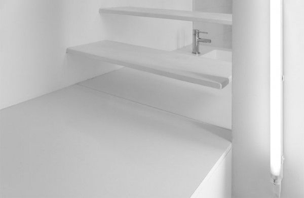 The kitchen sink can be seen through the stair risers which are lit by florescent bulbs from the side.