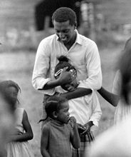 Stokely Carmichael & young children while SNCC marched for Civil Rights.  SNCC = Student Non-Violent Coordinating Committee.