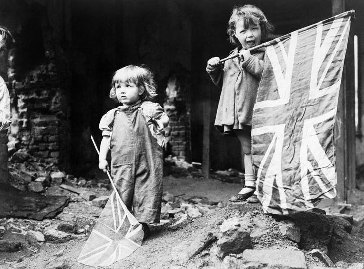 VE DAY IN LONDON, 8 MAY 1945. Two small girls waving their flags in the rubble of Battersea, snapped by an anonymous American photographer.